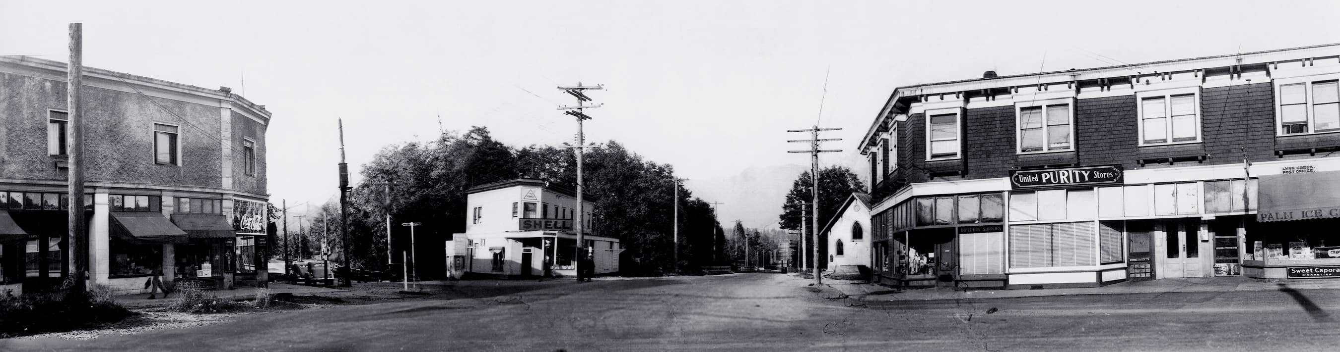 ca. 1950s. Panoramic image along Lynn Valley Road, across from Mountain Hwy. Buildings depicted from left to right: the Brier Block; the Triangle block; the Fromme block. Lynn Valley United Church can be seen behind the Fromme block. This image was taken after the streetcar lines had been removed.